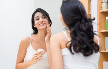 woman stands before a mirror takes care of the skin